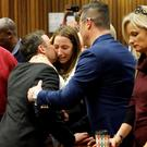Oscar Pistorius hugs his sister Aimee (far right) before being taken away from court Photo: AP