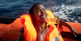 A woman cries after losing her baby in the water as she sits in a rescue boat off Lampedusa, Italy. Photo: Getty
