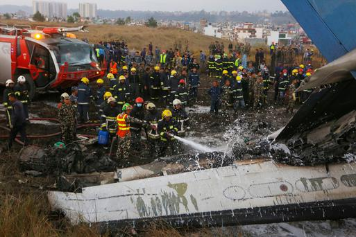 Nepalese firemen spray water on the debris after a passenger plane from Bangladesh crashed at the airport in Kathmandu, Nepal. Photo: AP