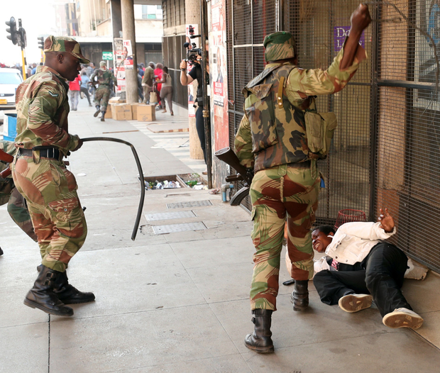 Soldiers beat a supporter of the opposition Movement for Democratic Change party in Harare, Zimbabwe. Photo: Reuters