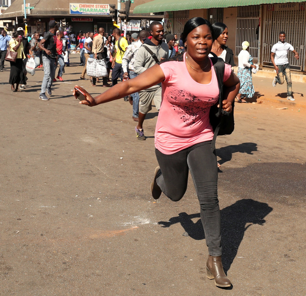 A woman flees as soldiers disperse protesters in Harare. Photo: Reuters