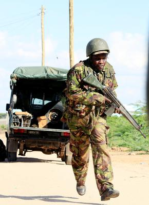 A Kenyan soldier runs for cover.