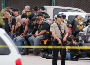 An armed officer stands guard as bikers wait to be questioned