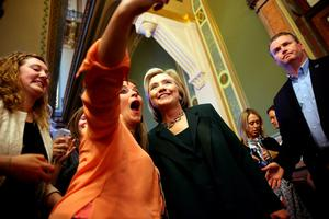 Hillary Clinton (R) stops to take a selfie after meeting with members of the Iowa State legislature at the Iowa State Capital .