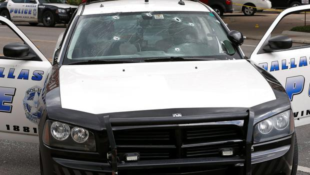 Bullet holes pierce the windshield of a police cruiser at Dallas Police Headquarters after an early morning attack on police by a gunman