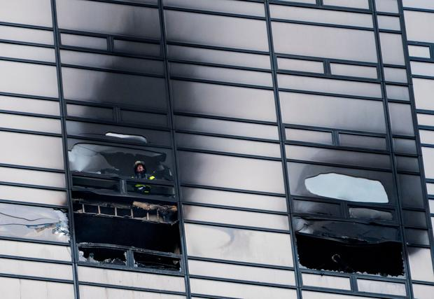 A firefighter looks out from the window of the fire-damaged apartment of the 50th floor of Trump Tower Photo: AP
