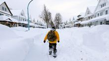 Brian Cintron walks in his snow-bound south Buffalo neighborhood. Snow has pounded the city for the third day.