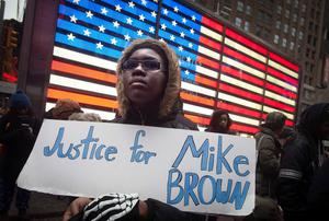 A protester holds a placard during a demonstration in Times Square, New York, following Monday's grand jury decision in the shooting of Michael Brown in Ferguson, Missouri