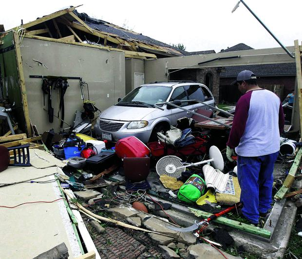 Pete Alaniz looks for items to salvage after a tornado hit in Cleburne, Texas