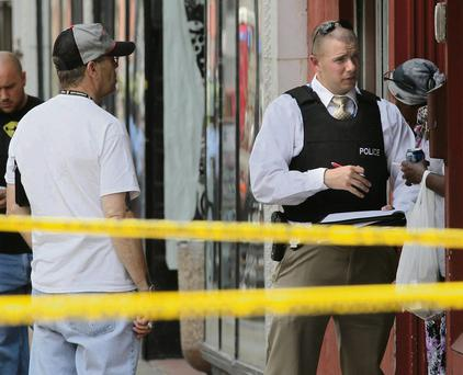 St. Louis police work the scene where four people were found dead in a business along Cherokee Street south of downtown in St. Louis