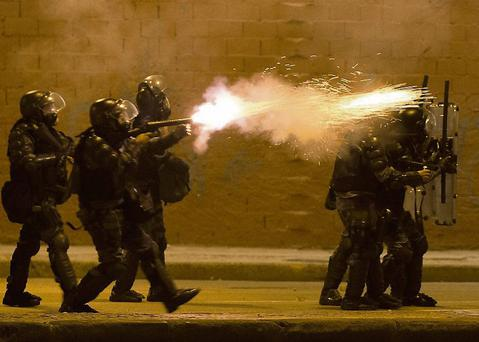 A military police fires tear gas at protestors during an anti-government demonstration in Rio de Janeiro, Brazil, Thursday, June 20, 2013. More than half a million Brazilians poured into the streets of at least 80 Brazilian cities Thursday in demonstrations that saw violent clashes and renewed calls for an end to government corruption and demands for better public services. Riot police battled protesters in at least five cities, with some of the most intense clashes happening in Rio de Janeiro, where an estimated 300,000 demonstrators swarmed into the seaside city's central area. (AP Photo/Victor R. Caivano)