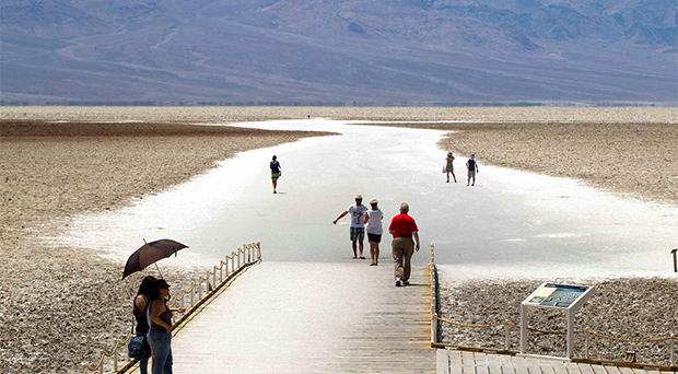 Women avoid the sun under an umbrella as high temperatures reach 128 degrees fahrenheit at Badwater Basin, 282 feet (85.5m) below sea level, in Death Valley National Park in California