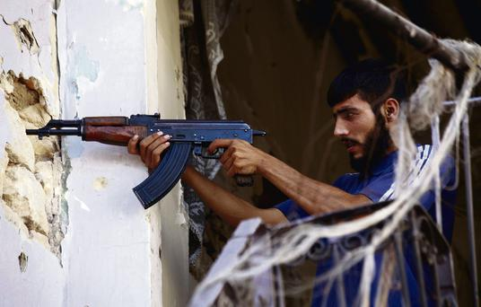 A Free Syrian Army fighter takes up a shooting position in Ogiwl, Aleppo