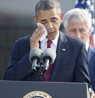 US President Barack Obama wipes his brow in the heat at an event on the 12th anniversary of the 9/11 attacks at the Pentagon near Washington