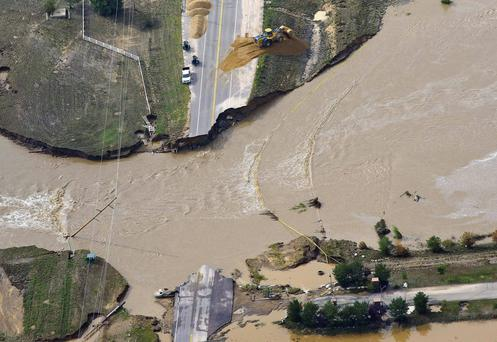 A section of highway is washed away by the flooded South Platte River in Colorado