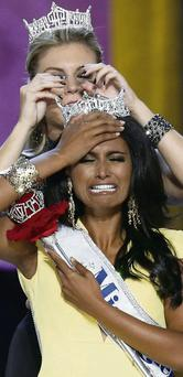 Aspiring doctor Nina Davuluri is overcome as she is crowned the 2014 Miss America by last year's winner Mallory Hagan