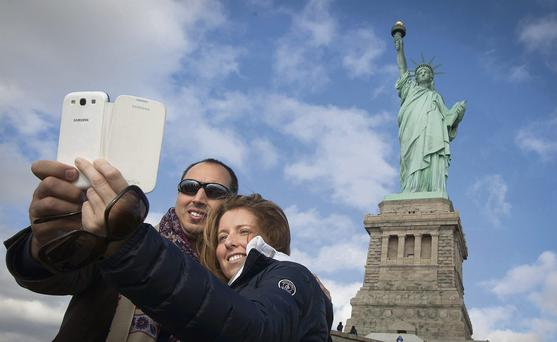 Massimiliano Manarinni and Elena Giacopello, from Italy, take a photo at the Statue of Liberty yesterday