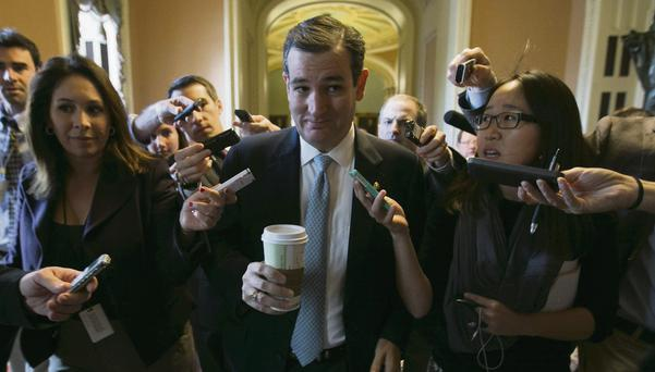 A sheepish looking Senator Ted Cruz is trailed by reporters in the US Capitol in Washington