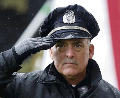 A Dallas police officer salutes during ceremonies in Dealey Plaza, where Dallas mayor Mike Rawlings spoke to the crowd to commemorate the 50th anniversary of JFK's death.