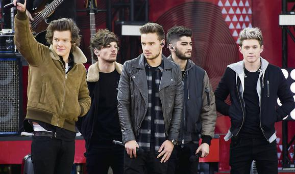 One Direction members, from left, Harry Styles, Louis Tomlinson, Liam Payne, Zayn Malik and Niall Horan wave to the crowd in New York.
