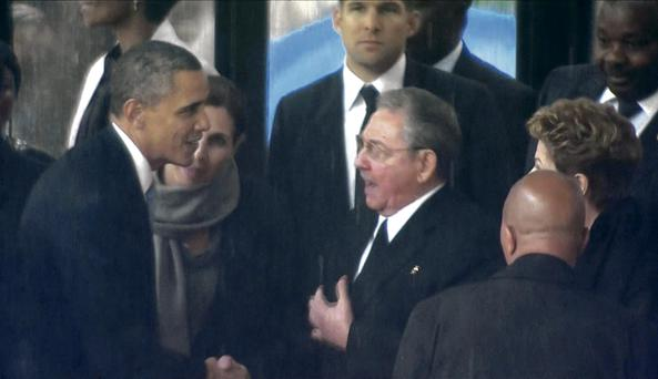 Barack Obama shakes hands with Cuban President Raul Castro at the FNB Stadium in Soweto, South Africa.