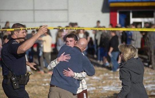 A student is reunited with his parents across from Arapahoe High School in Colorado.