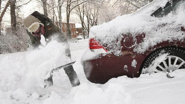 A man digs his car out of snow in Indiana