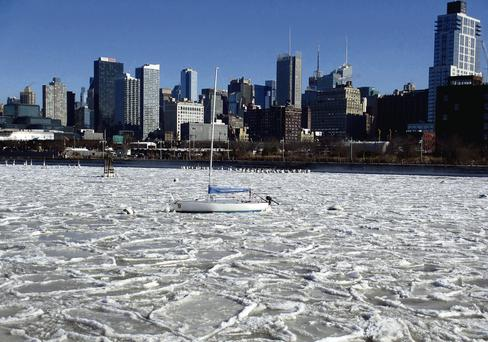 Ice floes cover the surface of the Hudson River to the west of Midtown Manhattan in New York.