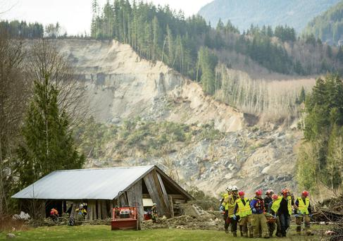 Rescue workers remove one of a number of bodies from the wreckage of homes destroyed by a mudslide near Oso, Washington state yesterday.