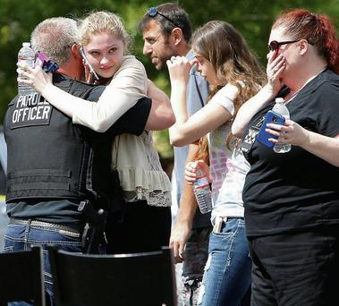 Students and parents are reunited in a supermarket car park after the shooting at the school.
