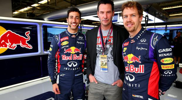 Actor Keanu Reeves poses with Sebastian Vettel of Germany and Infiniti Red Bull Racing and Daniel Ricciardo of Australia and Infiniti Red Bull Racing in the team garage after final practice for the United States Formula One Grand Prix at Circuit of The Americas in Austin, United States