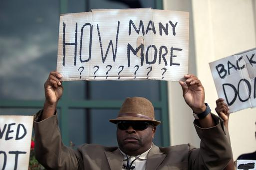 Reverend A Prioleau of Goose Creek, South Carolina, carries a sign at a rally in North Charleston