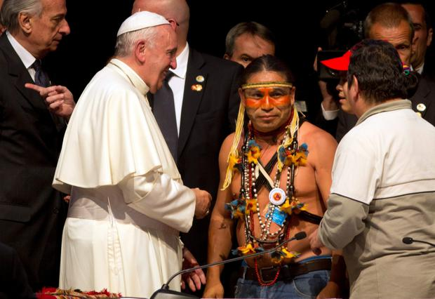 Pope Francis talks to Indian leaders on his visit to Bolivia, where he slammed capitalism as the 'dung of the devil'