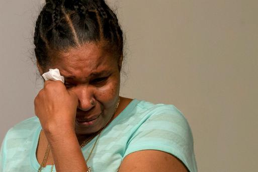 Esaw Garner, widow of Eric Garner, wipes away a tear at a news conference in New York
