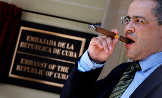 A member of the Bolivian delegation smokes a Cuban cigar outside the new Cuban Embassy building after its inauguration ceremony in Washington