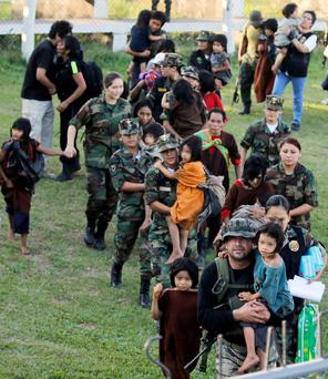 Peruvian Army members ushering adults and children to helicopters at the Air Force base in the jungle town of Mazamari, after their liberation by the armed forces from captivity by the Maoist guerrilla group Shining Path.