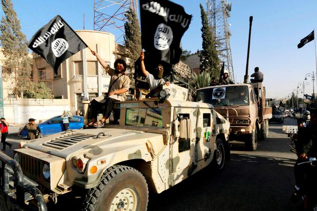 Isil members take part in a military parade along the streets of Syria's northern Raqqa province.