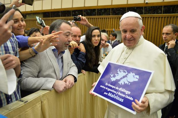 Pope Francis holds a poster reading 'It's time for Argentina and Britain to discuss the Malvinas' at the Vatican