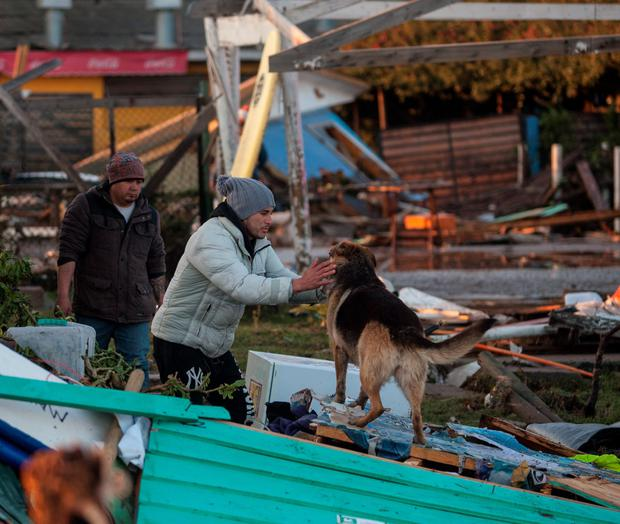 People recover their belongings in Concon some 110 km northwest Santiago after a massive earthquake . Santiago, Chile. The 8.3-magnitude earthquake that struck Wednesday off the coast of Chile has left at least eight dead, a million evacuated and one perso