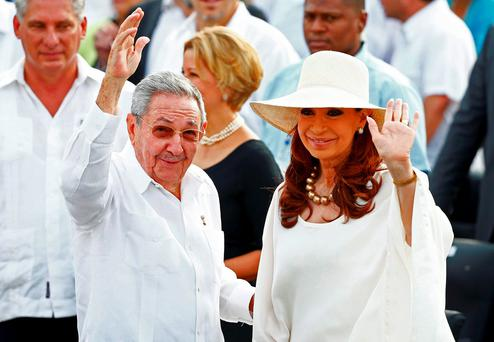 Cuba's President Raul Castro waves alongside Argentina's President Cristina Fernandez de Kirchner as they arrived to attend the first mass of the visit to Cuba by Pope Francis in Havana's Revolution Square