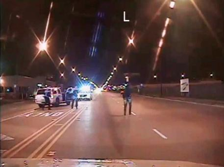 Laquan McDonald (R) walks on a road before he was shot 16 times by police officer Jason Van Dyke in Chicago