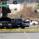 A police officer picks up a weapon from the scene of the investigation around the area of the SUV vehicle where two suspects were shot by police following a mass shooting in San Bernardino, California .