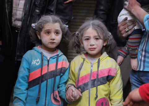 Girls who survived what activists said was a ground-to-ground missile attack by forces of Syria's President Bashar al-Assad, hold hands at Aleppo's Bab al-Hadeed district yesterday. Photo: Reuters