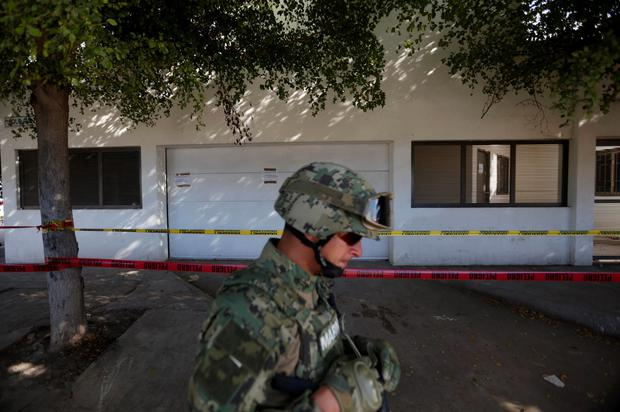 A soldier patrols outside the house in in Mexico where Guzman was recaptured. Photo: Reuters