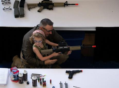 A man shows a young girl how to hold an airsoft gun during a National Rifle Association youth day in Houston, Texas. In his State of the Union speech on Tuesday evening, Barack Obama said he would 'keep pushing for progress on the work that still needs doing' including 'protecting our kids from gun violence'. Reuters