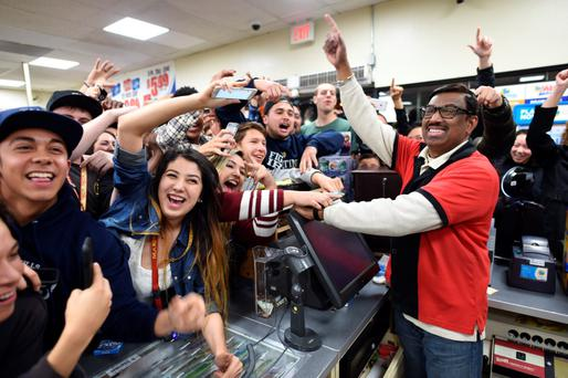 7-Eleven clerk M Faroqui celebrates with customers in Chino Hills after learning the store sold a winning Powerball ticket. Photo: AP