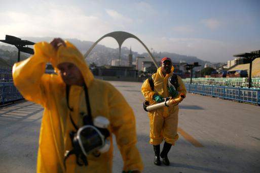 Municipal workers walk after spraying insecticide at Sambodrome in Rio de Janeiro. Photo: Reuters