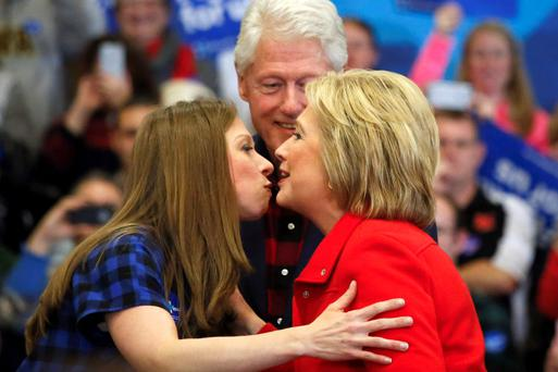 Hillary Clinton kisses daughter Chelsea Clinton as husband Bill Clinton looks on during a rally in Cedar Rapids, Iowa. Photo: Reuters