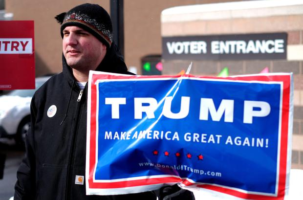 A supporter of US Republican presidential candidate Donald Trump displays a campaign poster