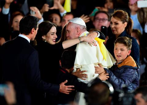 Pope Francis is embraced next to Mexican President Enrique Pena Nieto (L) and First Lady Angelica Rivera (R) at the airport in Ciudad Juarez, Chihuahua state, Mexico.